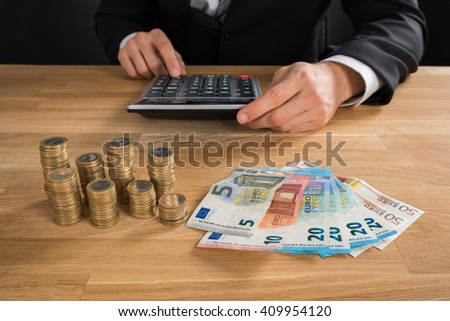 Close-up Of Young Businessman Using Calculator With Coins And Banknotes On Desk - stock photo
