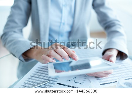 Close-up of young businesswoman hands working with touchpad - stock photo