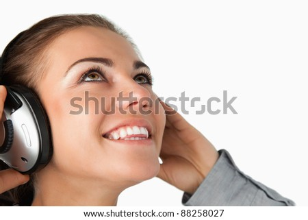 Close up of young businesswoman listening to music against a white background