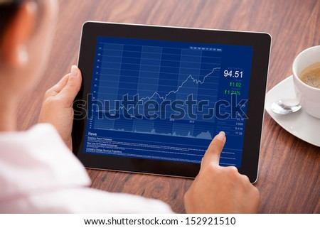 Close-up Of Young Businesswoman Looking At Graph On Digital Tablet - stock photo
