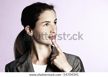 Close-up of young businesswoman thinking whilst looking upwards and holding finger against chin, isolated on pink background. - stock photo