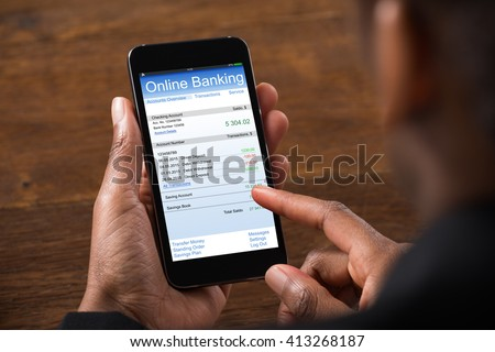 Close-up Of Young Businesswoman Using Online Banking On Mobile Phone In Office