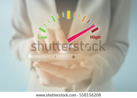 Close-up Of young businesswoman using smartphone with High Risk meter