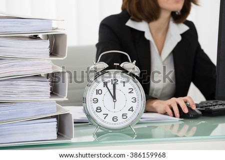 Close-up Of Young Businesswoman Working On Computer In Office With Alarm Clock On Desk - stock photo