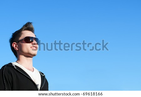 Close up of young casual cheerful man over blue sky