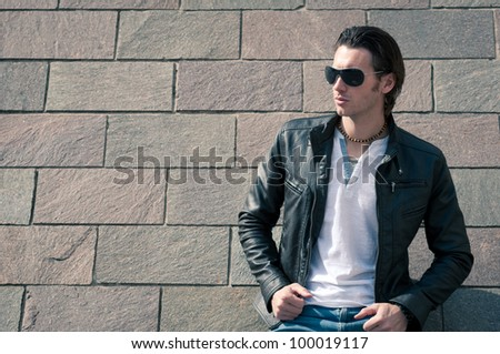 Close up of Young casual man portrait against wall.