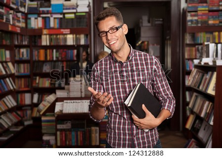 close-up of young caucasian handsome guy with eyeglasses and book in his hands, in a bookstore