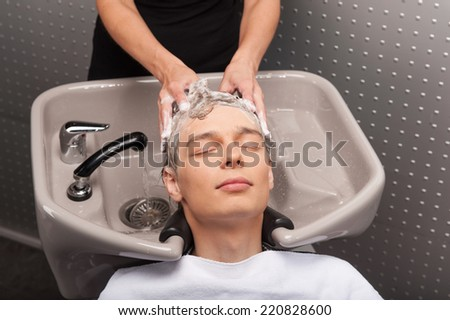 Close-up of young caucasian man having his hair washed. Portrait of male client getting his hair washed at salon - stock photo