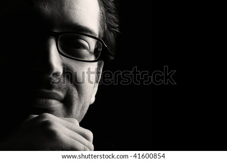 Close-up of young content man resting chin on fist, low key, black and white - stock photo