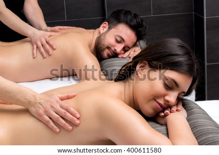 Close up of young couple enjoying therapeutic body massage together.