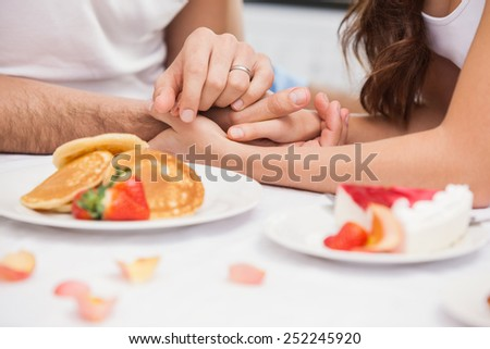 Close up of young couple having a romantic breakfast at home in the kitchen - stock photo