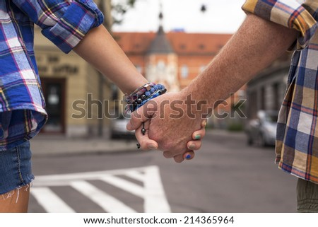Close-up of young couple holding hands, journey to Europe. - stock photo