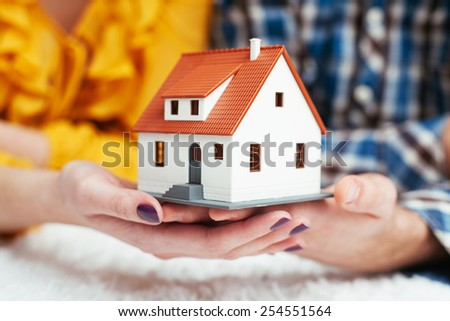 Close-up of young couple holding house miniature