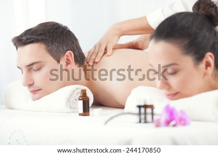 Close-up of young couple receiving backmassage at day spa - stock photo