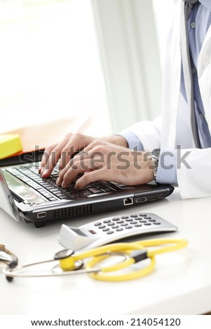 Close-up of young doctor preparing medical report at clinic. - stock photo
