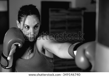 Close-up of young female boxer practicing in gym while wearing boxing gloves. Black and white - stock photo