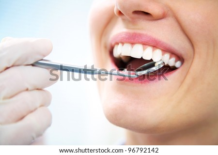Close-up of young female having her teeth examinated - stock photo