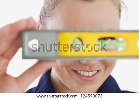 Close-up of young female technician holding spirit level over white background