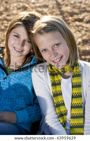 Close-up of young friends (10-11 years) posing together outdoors on playground - stock photo