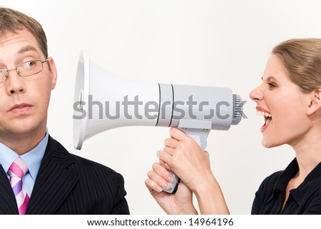 Close-up of young furious woman screaming at her boss through megaphone