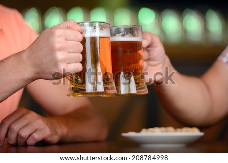 Close-up of young gay men to hold glasses of beer in a beer pub - stock photo