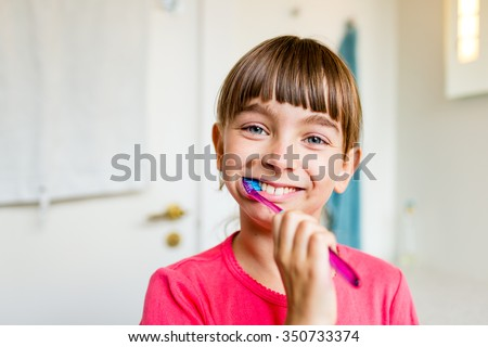 Close-up of young girl brushing her teeth with toothbrush while standing in bathroom with natural daylight. - stock photo