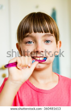 Close-up of young girl brushing her teeth with toothbrush while standing in bathroom with natural daylight.