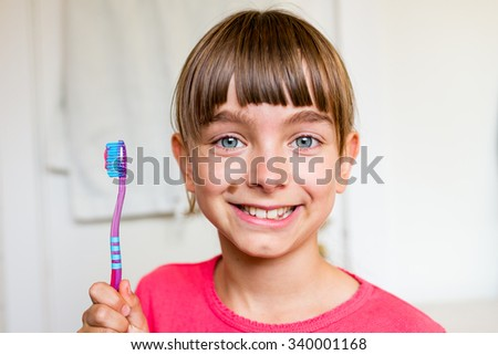 Close-up of young girl holding toothbrush in her hand ready for brushing her teeth while standing in bathroom. - stock photo