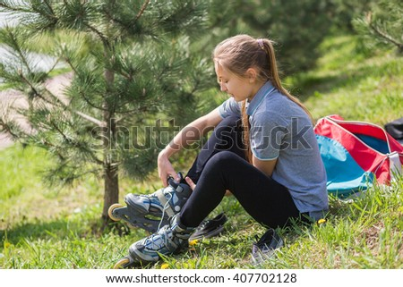 Close-up Of  Young Girl Legs Wearing Roller Skating Shoe, Outdoors - stock photo