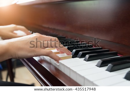 Close up of young girls hands, playing piano. - stock photo