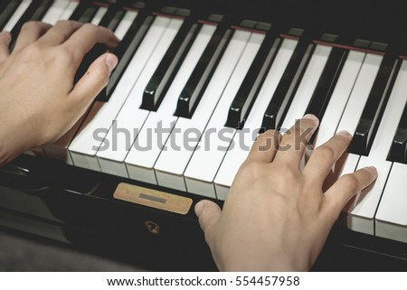 Close up of young girls hands, playing piano.