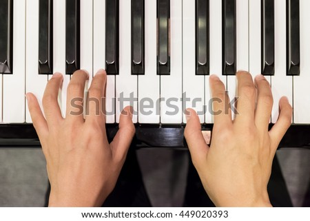 Close up of young girls hands, playing piano. vintage tone filte