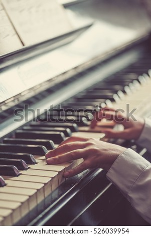 Close up of young girls hands, playing piano. Vintage tone filter effected. Soft focus