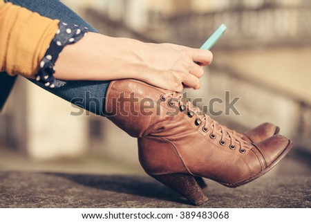 Close up of  young handsome caucasian woman holding a smartphone, tapping the screen - technology, social network, communication concept - stock photo