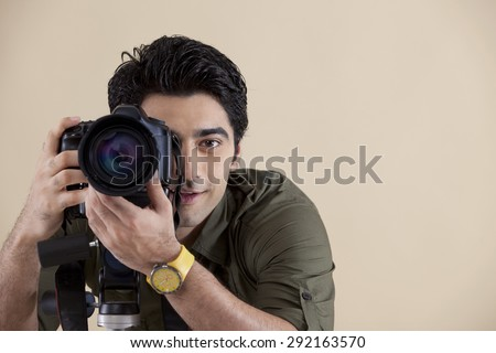 Close-up of young handsome photographer taking a photograph - stock photo