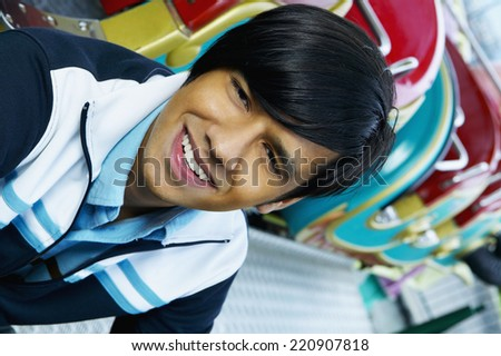 Close up of young Hispanic man smiling next to carnival ride - stock photo