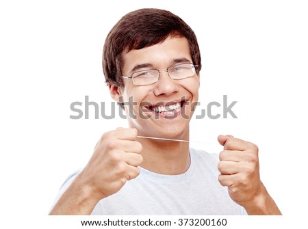 Close up of young hispanic man wearing glasses holding dental floss near his toothy smile with perfect healthy white teeth isolated on white background - dental care and hygiene concept - stock photo