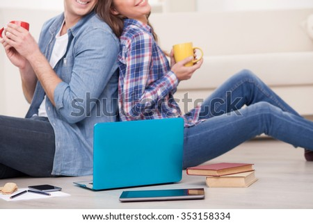 Close up of young husband and wife drinking coffee at home. They are sitting on floor and watching a notebook. The man and woman are smiling - stock photo