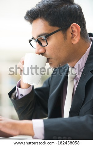 close up of young indian business man enjoying coffe during work - stock photo