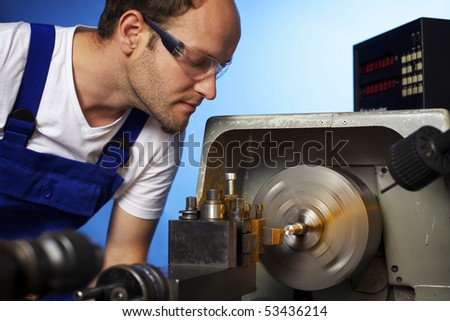 Close-up of young male technician in blue overall working on lathe machine in workshop, isolated on blue background. - stock photo