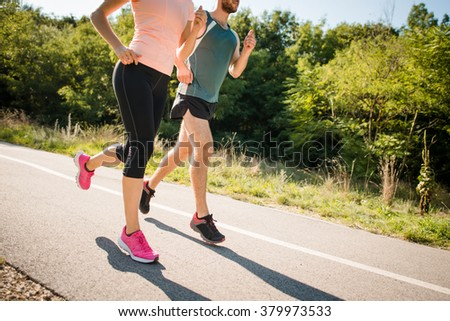 Close up of young man and woman jogging together in park on summer sunny day
