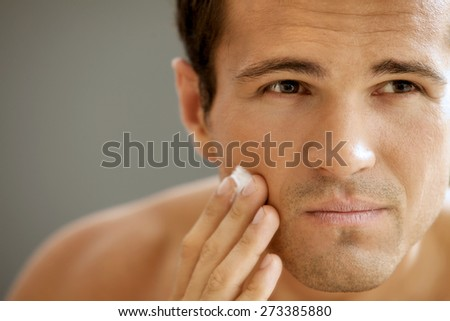 Close-up of young man applying shaving cream - stock photo