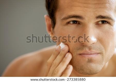 Close-up of young man applying shaving cream - stock photo