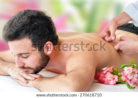 Close up of young man enjoying back massage. Young man laying face down and therapist hands massaging lower back. - stock photo