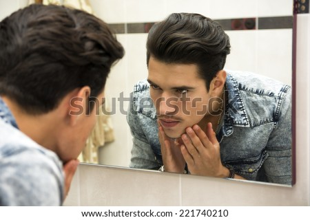 Close Up of Young Man Examining Face in Reflection of Mirror and Glaring at Self - stock photo