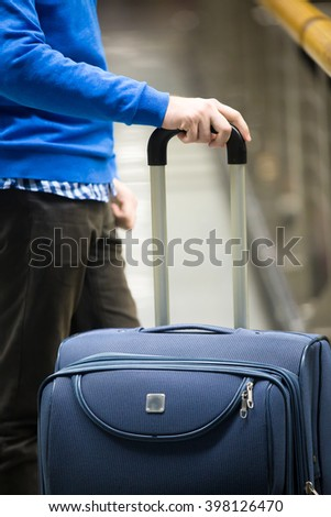 Close-up of young man hands holding suitcase in modern airport terminal. Travelling guy wearing smart casual style clothes standing with his luggage while waiting for transport. Vertical image - stock photo