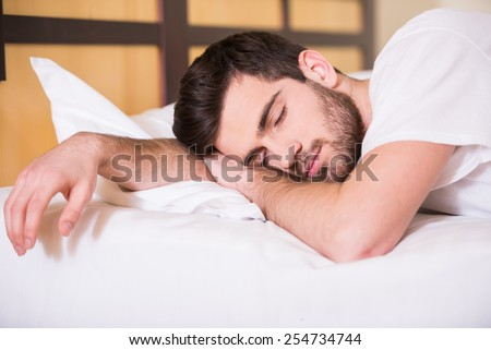 Close-up of young man is sleeping on bed. - stock photo