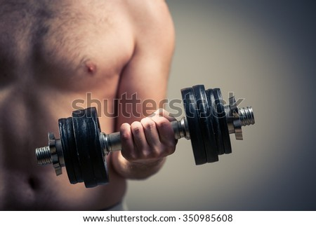 Close up of young man lifting weights over grey background - stock photo