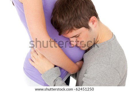 Close-up of young man listening carefully the belly of his wife against a white background