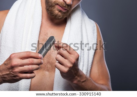 Close up of young man polishing his nails with fine. He is standing with white towel. Isolated - stock photo